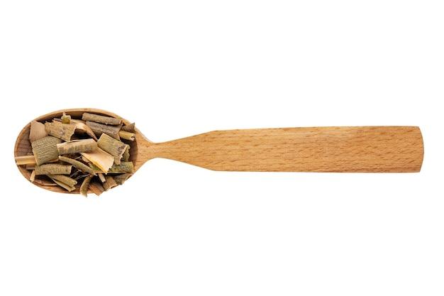 Corteza de sauce seca en una cuchara de madera sobre un fondo blanco. fitoterapia y prevención de enfermedades.