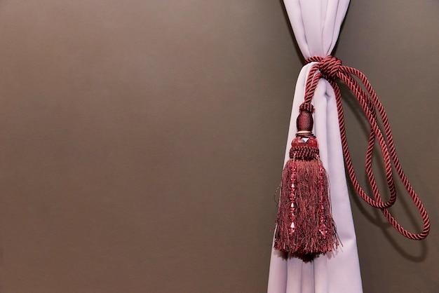 La cortina está montada con una cuerda con flecos rojos. copia espacio