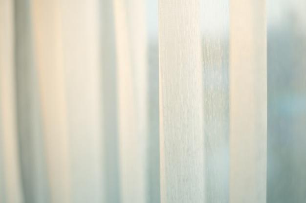Cortina de tela blanca con la luz del sol de iluminación.