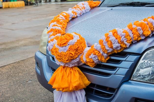 Cortinas anaranjadas y blancas. flores atadas al automóvil.