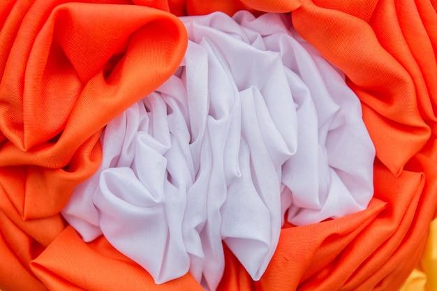 Las cortinas anaranjadas y blancas hicieron las flores, fondo de la textura.