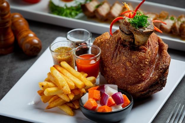 Corvejón de cerdo en alemán con salsas sobre fondo oscuro
