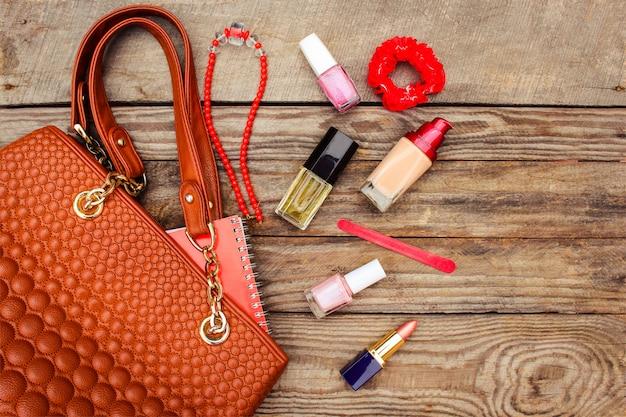 Cosas del bolso de dama abierto. bolso de mujer en mesa de madera. imagen tonificada