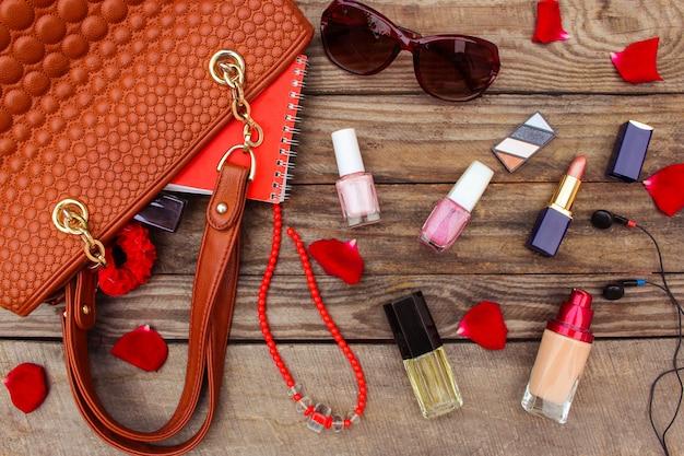Cosas del bolso de señora abierto. bolso de mujer sobre madera. imagen entonada
