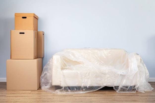 Cosas domésticas empacadas en cajas y sofá empacado para mudarse