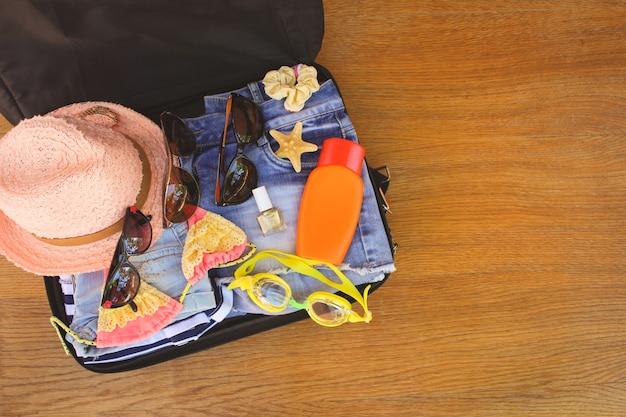 Cosas de familia y accesorios de verano en maleta. imagen entonada vista superior.