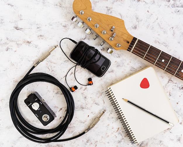 Cosas de musica. guitarra, pedal de guitarra, auriculares, teléfono móvil en blanco