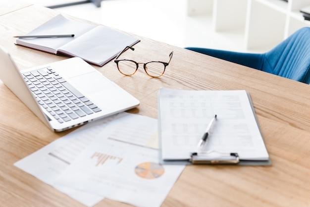 Cosas de oficina sobre mesa de madera. portátil, portapapeles, gafas, lápiz, cuaderno. lugar de trabajo sin nadie