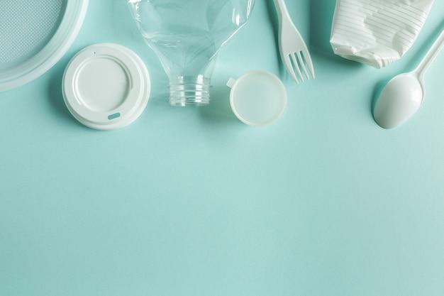 Las cosas de plástico en bruto secundarias para reciclar planas yacían sobre papel azul con espacio de copia
