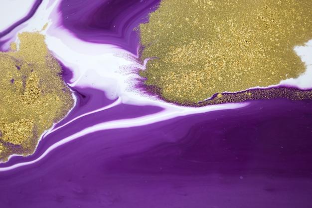 Cose up glitter dorado sobre fondo de tintas púrpuras mezcladas líquidas