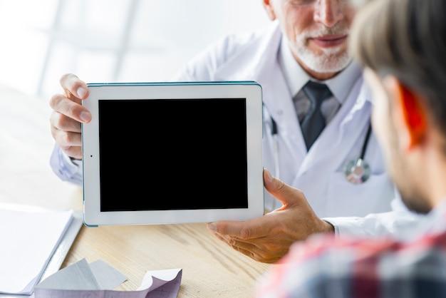 Cosecha doctor mostrando tableta al paciente