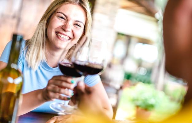 Cosecha inclinada de pareja feliz brindando vino tinto en el restaurante de la campiña