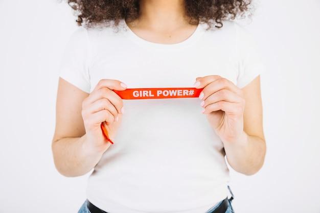 Cosecha mujer sosteniendo la cinta con la escritura de poder chica Foto gratis