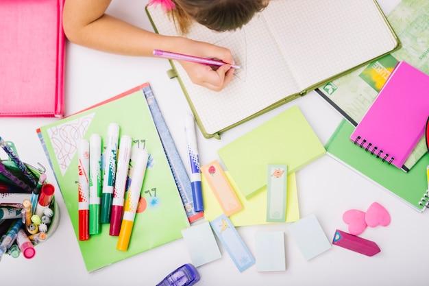 Cosecha de niño en la mesa con los útiles escolares