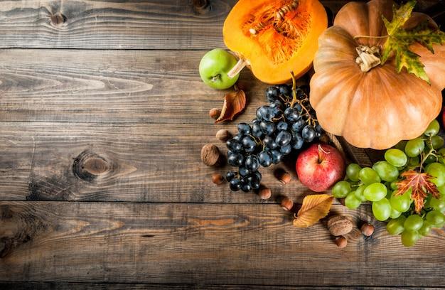 Cosecha de otoño y acción de gracias. frutas de otoño estacionales y calabaza en mesa de madera, vista superior de copyspace