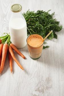 Cosecha de zanahoria de granja situada cerca de la botella de leche y el vaso lleno de leche y jugo fresco natural con pajita dorada