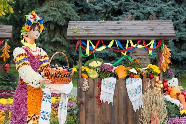 Coseche las verduras en el comercio justo en un pabellón de madera. maniquí femenino con cesta llena de frutas. productos agrícolas, mercado rural.