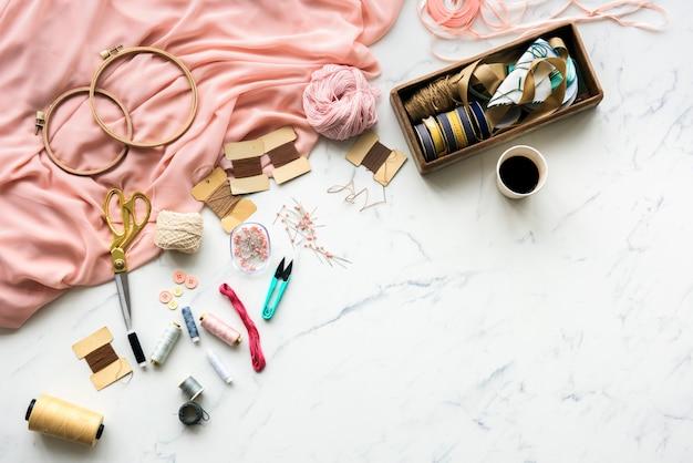 Coser con aguja objetos hechos a mano en mesa de mármol.