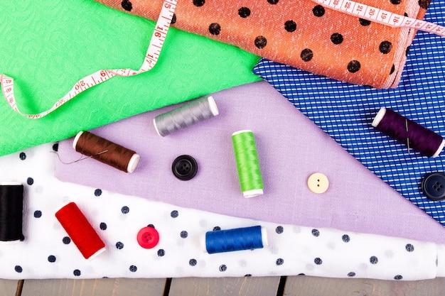 Coser botones, carretes de hilo y tela sobre mesa de madera.