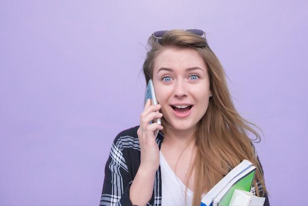 Coseup retrato de una niña sorprendida hablando por teléfono y mirando a la cámara sobre un fondo morado.