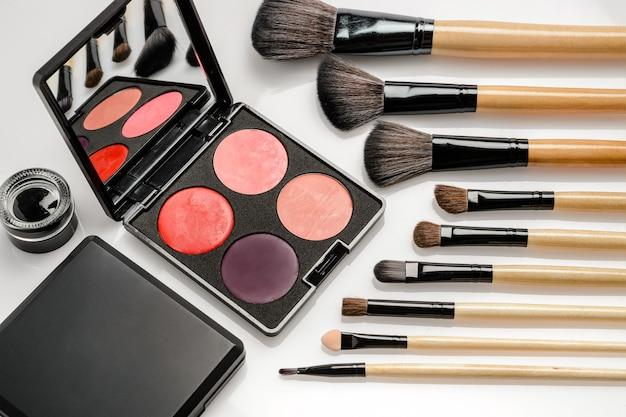 Cosmética decorativa para maquillaje de ojos, paleta con colores brillantes y pinceles cosméticos.