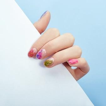 Cosmética de manos para colorear y cuidar las uñas, manicura profesional y producto para el cuidado. mano recostada sobre un fondo de papel de colores