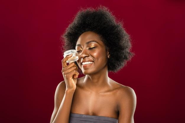Cosmética natural. encantado de mujer joven sonriendo mientras usa crema facial orgánica