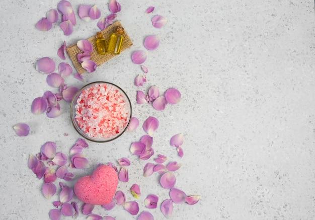 Cosmética orgánica con aceite de rosa sobre fondo gris.