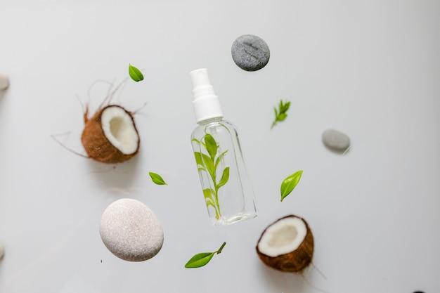 Cosmética orgánica con extractos de hierbas y coco sobre fondo gris.