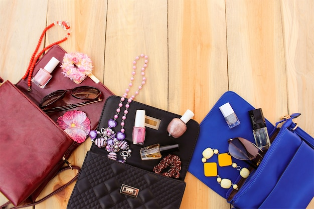 Cosméticos y accesorios de mujer cayeron de diferentes bolsos. cosas del bolso de señora abierto.