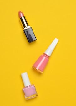 Cosméticos y accesorios de mujer para el cuidado de la belleza sobre un fondo amarillo pastel. esmalte de uñas, lápiz labial, vista superior, tendencia minimalista