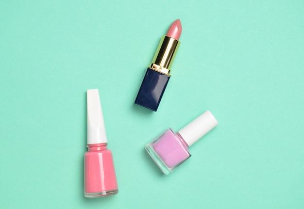 Cosméticos y accesorios de mujer para el cuidado de la belleza sobre un fondo azul pastel. esmalte de uñas, lápiz labial, vista superior, tendencia minimalista