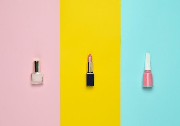 Cosméticos y accesorios de mujer para el cuidado de la belleza sobre un fondo de color pastel esmalte de uñas, lápiz labial, vista superior, tendencia minimalista