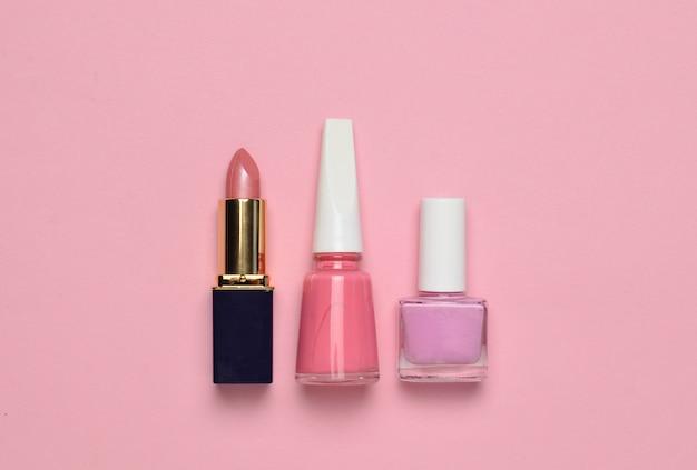 Cosméticos y accesorios de mujer para el cuidado de la belleza sobre un fondo rosa pastel. esmalte de uñas, lápiz labial, vista superior, tendencia minimalista