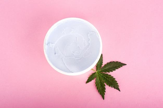 Cosméticos de cannabis, crema de marihuana natural y hojas verdes sobre fondo rosa belleza.