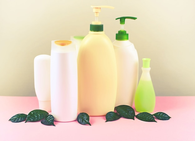 Cosméticos para el cuidado del cabello y el cuerpo botellas blancas sobre fondo gris.