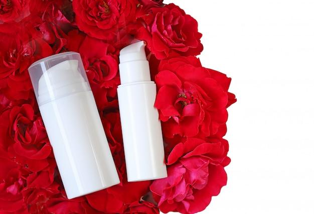 Cosméticos y cuidado de la piel mocap. crema y suero con extracto de rosa en frascos de cosméticos blancos sobre pétalos de rosas rojas aisladas. concepto de cosmética orgánica