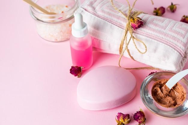 Cosméticos para el cuidado de la piel con sabor a rosa, jabón, aceite, mascarilla y sal de baño sobre fondo rosa con rosas.
