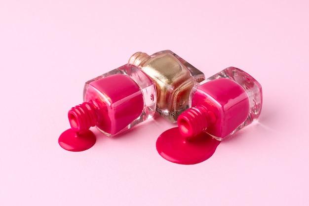 Cosméticos esmaltes de uñas rosas y dorados en rosa
