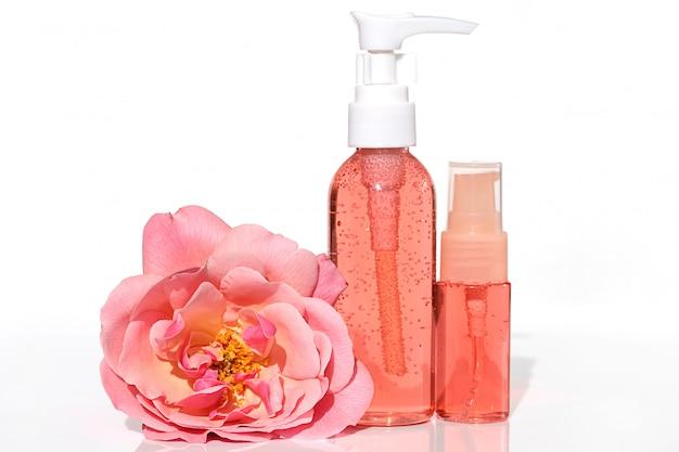 Cosméticos con extracto de rosa. gel y tónico de color rosa con extracto de rosa en una botella de plástico y felpa rosa grande flor rosa