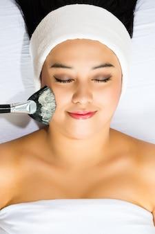 Cosméticos - mujer asiática recibe una máscara facial