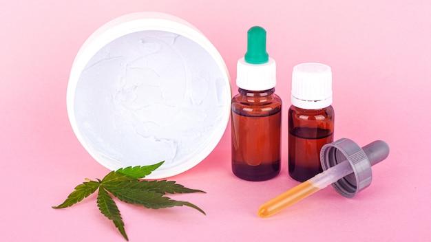 Cosméticos naturales de cannabis, crema orgánica para manos y cuerpo a partir de extracto de marihuana sobre un fondo de belleza rosa.