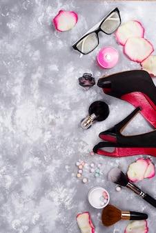 Cosméticos en perfumes y zapatos sobre un fondo gris con espacio de copia
