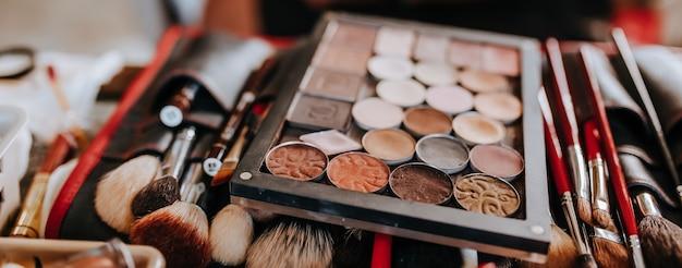 Los cosméticos y los pinceles de maquillaje se encuentran durante el trabajo del maquillador.