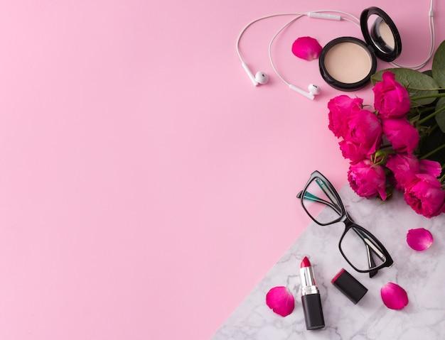 Cosméticos, pinceles de maquillaje, pintalabios, polvos y lentes con flores en el moderno mármol rosa.