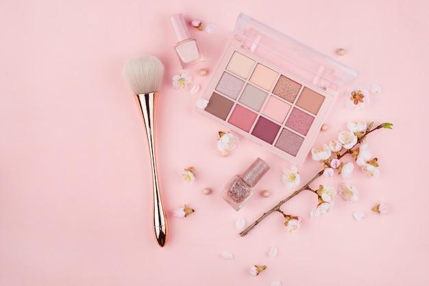 Cosméticos y sakura rama en una pared de color rosa. concepto de belleza, endecha plana.