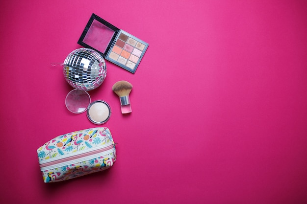 Cosméticos sobre fondo rosa. imagen colorida para el tema de cosméticos. polvo, resaltador, pincel, sombras de ojos y bolsa de cosméticos sobre fondo rosa.