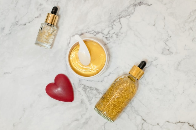 Cosméticos de spa sobre fondo de mármol. blogger de belleza. copyspace.beauty productos para el cuidado de la piel. aceite, crema, suero, frasco de parche para ojos cosméticos de hidrogel dorado.