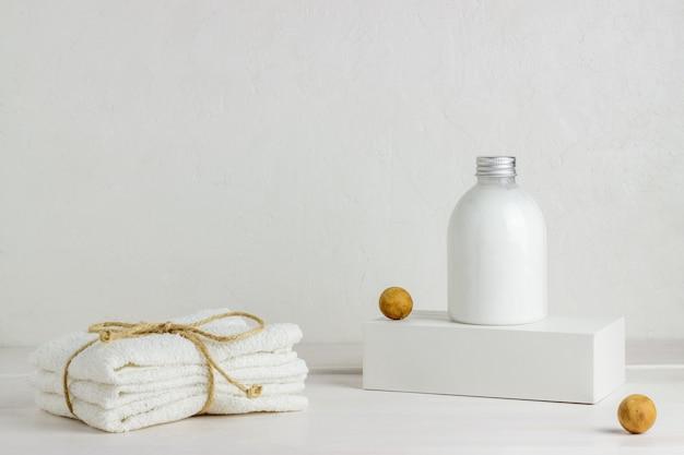 Cosméticos y toallas sobre un fondo blanco. diseño. concepto mínimo.