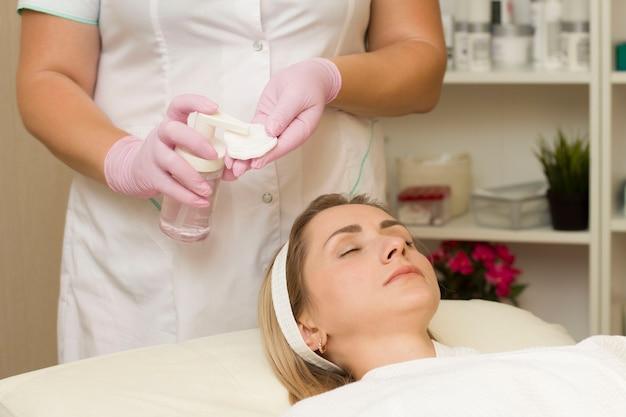 La cosmetóloga aplica agua micelar a la esponja. limpiar el rostro. en una cita con un cosmetólogo.